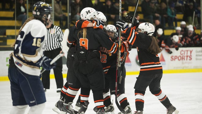 Middlebury celebrates a goal during the Division I high school girls hockey championship between the Middlebury Tigers and the Essex Hornets at Gutterson Fieldhouse on Tuesday night .