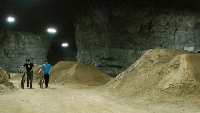 In this Jan. 21 photo, bicycle riders Brad Titzer, left, and Derek Fetko walk their bikes during a test run through a new underground bike park in Louisville, Kentucky. The course is built inside an old limestone mine that has become a tourist attraction in Louisville in recent years. (AP)