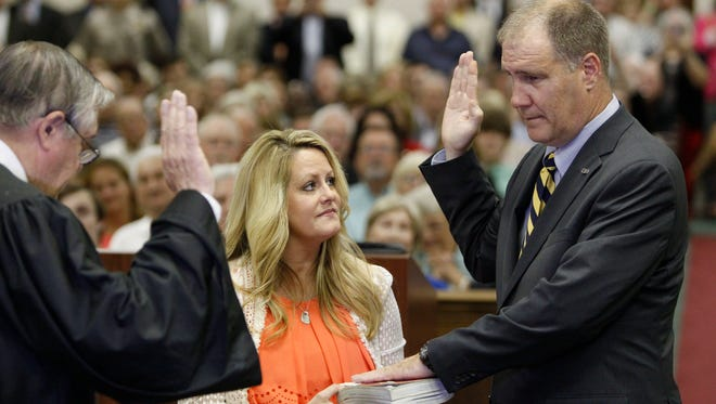 Shelia Kelly, center, holds the bible for her husband and newly elected Trent Kelly, right, as he takes the ceremonial oath of office for Mississippi's 1st Congressional District from Northern District of Mississippi Federal Judge Glen Davidson on Monday, June 8, 2015 at the Lee County Justice Center in Tupelo, Miss.