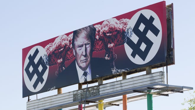 A billboard depicting President Donald Trump flanked by Nazi-inspired imagery and mushroom clouds is displayed at the corner of Grand Avenue and Taylor Street in Phoenix on March 19, 2017. Artist Karen Fiorito created the piece on commission from La Melgosa, a Phoenix art gallery, and has received death threats for the work.