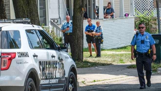 Lansing Police Department and Ingham County sheriff deputies surround a house on Bailey Street in Lansing after trying to apprehend a suspect who led them on a car and foot chase on Sunday, July 30, 2017.