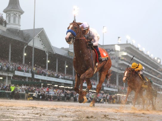 Mike Smith aboard Justify crosses the finish line to