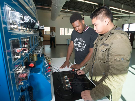 Pensacola High School students Kadarrious Lewis, left, and Olygen Quizon, right, use lab equipment to learn about the manufacturing process.