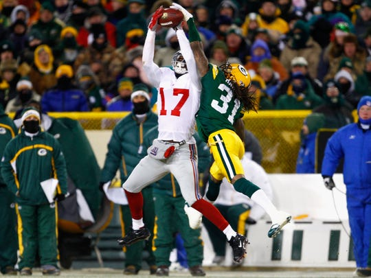 GREEN BAY, WI - JANUARY 20:  Wide receiver Plaxico Burress #17 of the New York Giants catches a 32 yard reception over Al Harris #31 of the Green Bay Packers during the second quarter of the NFC championship game on January 20, 2008 at Lambeau Field in Green Bay, Wisconsin.  (Photo by Jamie Squire/Getty Images)