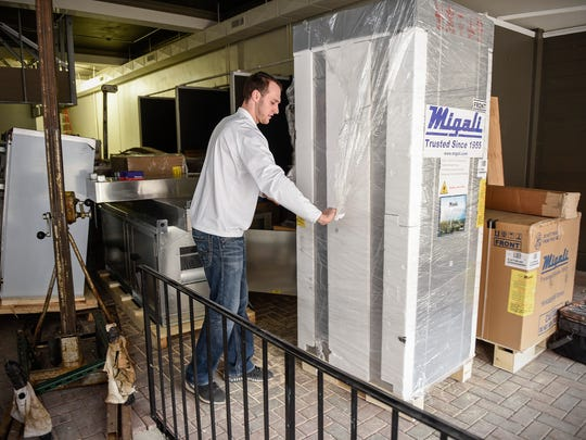 Travis Schertz, co-owner of Polito's Pizza, unwraps a new freezer Thursday, April 12, to be installed in the new location at 515 West St. Germain St.