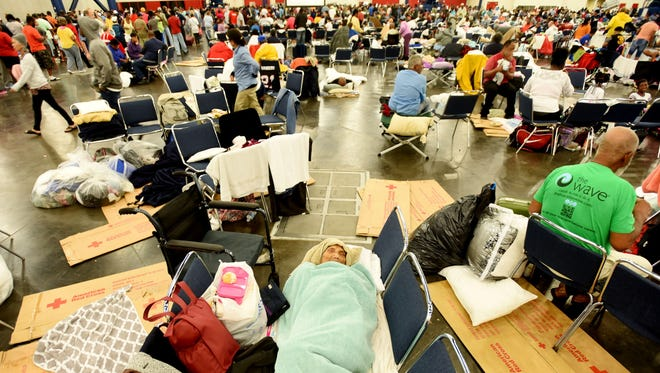 Yuth Chhut, 98, sleeps on chairs inside the Red Cross shelter at the George R. Brown Convention Center in Houston.