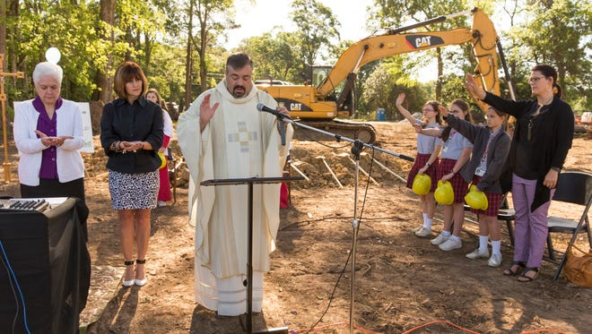 Rev. Brian Taylor offers a blessing during a mass and ceremony celebrating St. Genevieve Catholic School middle campus' groundbreaking for a new cafetorium in Lafayette April 7, 2016.