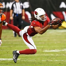 Arizona Cardinals wide receiver Larry Fitzgerald makes a first down catch against Cincinnati Bengals cornerback Leon Hall in the first half during preseason action on Sunday, Aug. 24, 2014, at University of Phoenix Stadium in Glendale, Ariz.