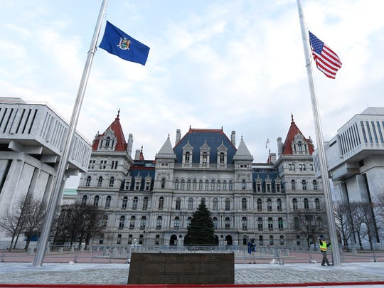 With the state Capitol in the background, Fred Ciampi and Robert Bongiorno of the Office of General Services lower the state and American flags to half-staff.