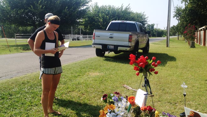 Sarah Harper, Christopher Lane's girlfriend, stands beside a memorial along the road in Duncan, Okla., where police say Lane, an Australian baseball player was shot and killed Friday.