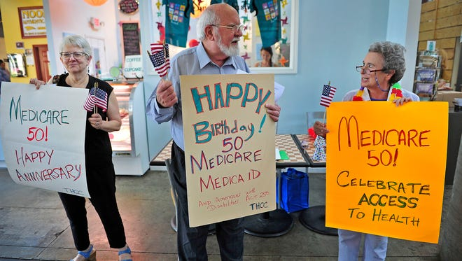 Susan Veale, from left, Walter Davis and Jackie Shrago hold signs to celebrate the 50th anniversary of Medicare and Medicaid on Thursday at the Nashville Farmers' Market.
