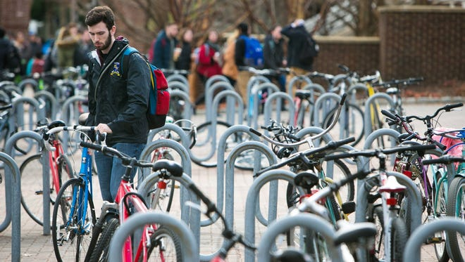 A bike rider grabs his bicycle parked along South College Avenue in Newark.