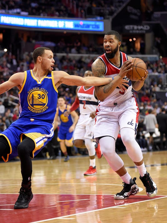 Washington Wizards forward Markieff Morris (5) drives to the basket against Golden State Warriors guard Stephen Curry (30) during the second half of an NBA basketball game, Tuesday, Feb. 28, 2017, in Washington. The Wizards won 112-108. (AP Photo/Nick Wass)