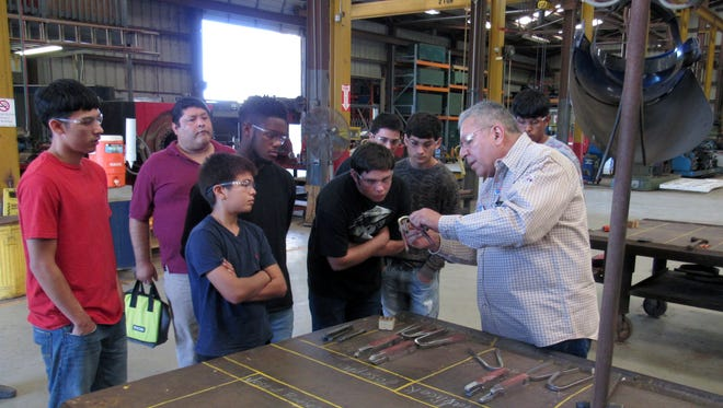 A welding technician at Base Line Data in Portland shows HELP students the various tools used to properly form pieces needed in a project.