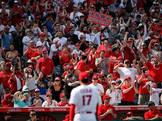 Fans cheer as Los Angeles Angels starting pitcher Shohei Ohtani (17), of Japan, heads to the dugout after the sixth inning of a baseball game against the Oakland Athletics, Sunday, April 8, 2018, in Anaheim, Calif. (AP Photo/Jae C. Hong)