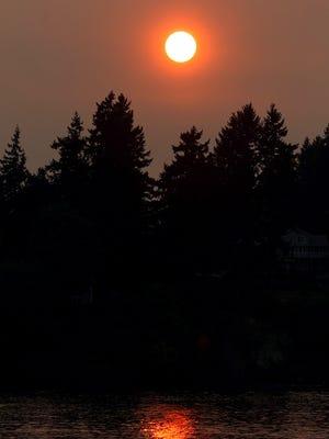 Karen Bevers, of Bremerton, paddles off Lions Park in Bremerton on Monday, as smoke filtered sunlight.