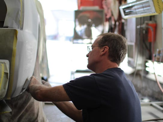 Ray Fetzner sands the primer on a Chevy truck before