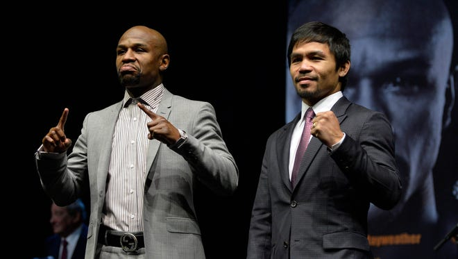 Floyd Mayweather, left, and Manny Pacquiao pose for photographers during a press conference to announce their fight.