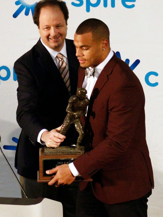 Mississippi State quarterback Dak Prescott, right, is awarded the Conerly Trophy by Hu Meena, president and CEO of C Spire Wireless, Tuesday, Dec. 1, 2015 in Jackson, Miss. Prescott is the second two-time winner of the award, which is given to the state's top college football player. (AP Photo/Rogelio V. Solis)