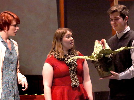 """Seymour (Dylan Hoppel) introduces Audrey II to Audrey (Julia Rosenquist) and Mrs.Mushnik (Anna Karius) during the first act of Kettle Moraine Performs' production of """"Little Shop of Horrors. Show dates are Feb. 22 and 23 at 7 p.m., and 1 p.m. and 7 p.m. on Feb. 24 at Kettle Moraine High School."""