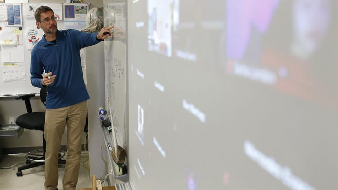 Scott Swain works with his high school physics class at Clarke Central High School in Athens, Ga., on Thursday, Sept. 24, 2020. Due to the ongoing COVID-19 pandemic, Clarke County schools are doing distance learning to start the 2020-21 school year.
