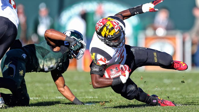 Maryland running back Wes Brown, right, is tripped up by Michigan State cornerback Darian Hicks at Spartan Stadium.