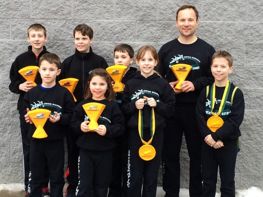 Members of the Central Wisconsin Speed Skating Club hold their trophies from the De Pere meet. They are, back from left, Bristol Kowal, Parker Faust, Everett Puent, Brian Puent, and front from left, Damien, Aubrey, Addison  and Griffin Puent.