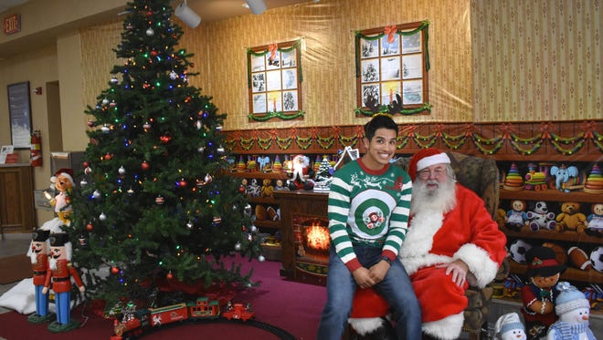 Michael Luna, a First National Bank associate, keeps Santa company as they wait for local children to visit Friday afternoon.