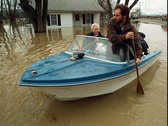 Steve Olgle paddles a boat as he helps Vicki Wright, left, to get to her home Tuesday, March 4, 1997, in Lebanon Junction, Ky.