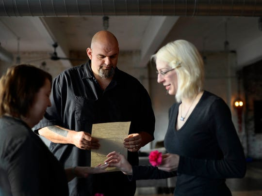 Mayor John Fetterman, center, officiates the wedding of Kayley Ryan, left, and Lindsey Shaner at his home in Braddock, Pa., Tuesday, December 22, 2015. Fetterman says he averages one wedding per week.