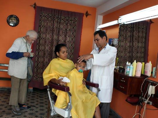 A barber works at his shop in Havana in December 2014.