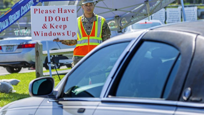 A National Guardsman holds a sign directing drivers to have their identification ready and to keep their windows up at the coronavirus testing sites at the FITTEAM Ballpark of the Palm Beaches in April.