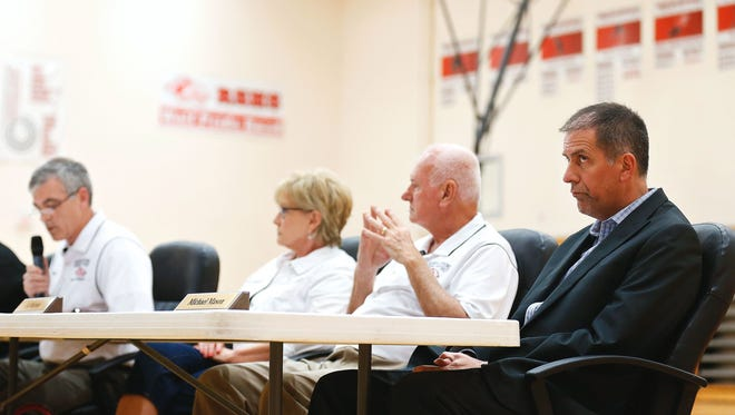 Reeds Spring school board president Earl Johnson, standing on far left, was named in a retaliation lawsuit filed in early July. He spoke during an April board meeting.