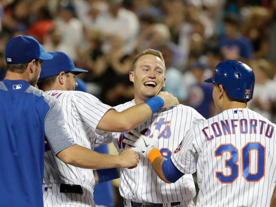 New York Mets' Brandon Nimmo (9) celebrates with teammates Kevin Plawecki and Michael Conforto (30) after hitting a walk-off three-run home run during the 10th inning of a baseball game against the Philadelphia Phillies on Wednesday, July 11, 2018, in New York. The Mets won 3-0.