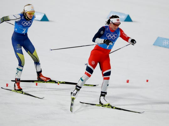 Marit Bjoergen, of Norway, right, and Stina Nilsson, of Sweden, compete during the women's 4 x 5km relay cross-country skiing competition at the 2018 Winter Olympics in Pyeongchang, South Korea, Saturday, Feb. 17, 2018. (AP Photo/Kirsty Wigglesworth)