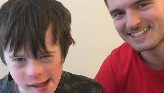 James Rink, 9, with Apple store worker Andrew Wall on the floor where James fell after smashing into a glass wall