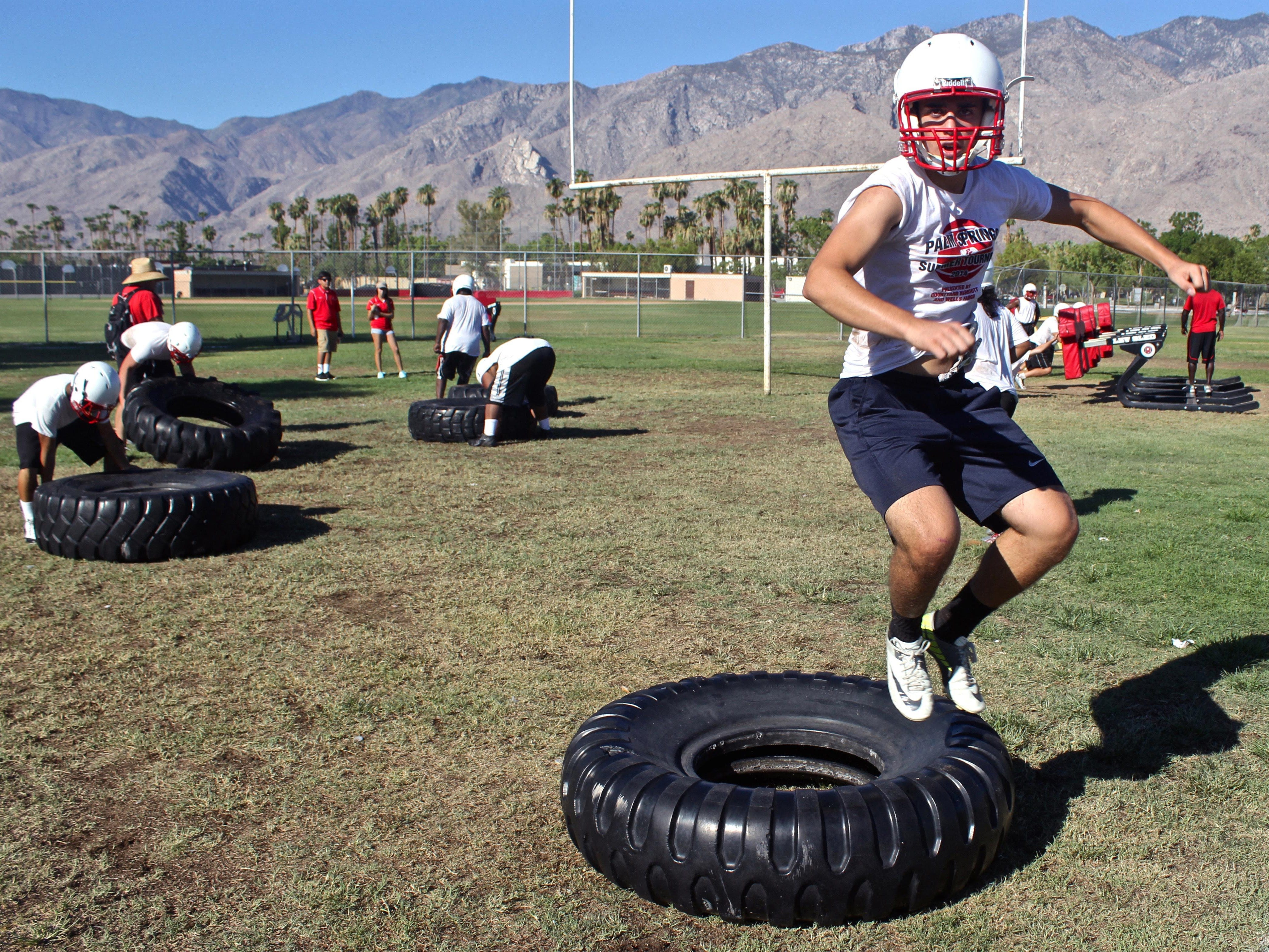 A group of Palm Springs High School students do a series of tire exercises during the squad's third mandatory training session, Tuesday, at the Indians' practice field.