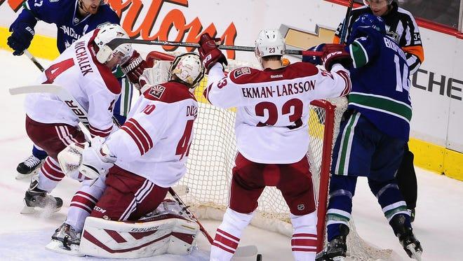 Vancouver's Alexandre Burrows scores against Arizona Coyotes goaltender Mike Smith on Monday.