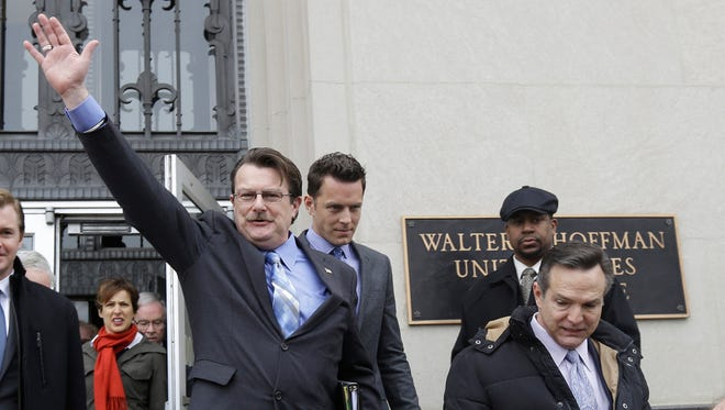 In this Feb. 4, 2014 file photo, plaintiff in the Bostic v. Schaefer case, Tony London, waves to the crowd as he and his partner, Tim Bostic, right, leave Federal Court after a hearing on Virginia's ban on gay marriage in Norfolk, Va. On Wednesday, Aug. 13, 2014, a federal appeals court refused to delay its ruling striking down Virginia's gay marriage ban.