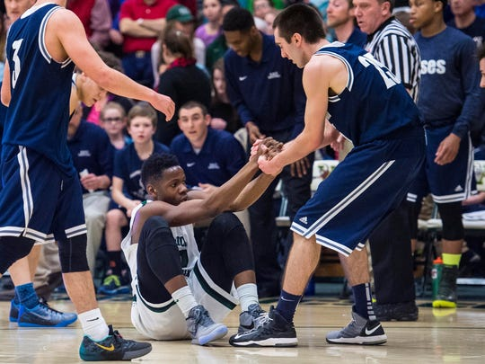 Burlington's Josh Hale (right) helps Rice's Ben Shungu to his feet during the D-1 boys state basketball championship at Patrick Gymnasium in Burlington on Saturday, March 7, 2015.