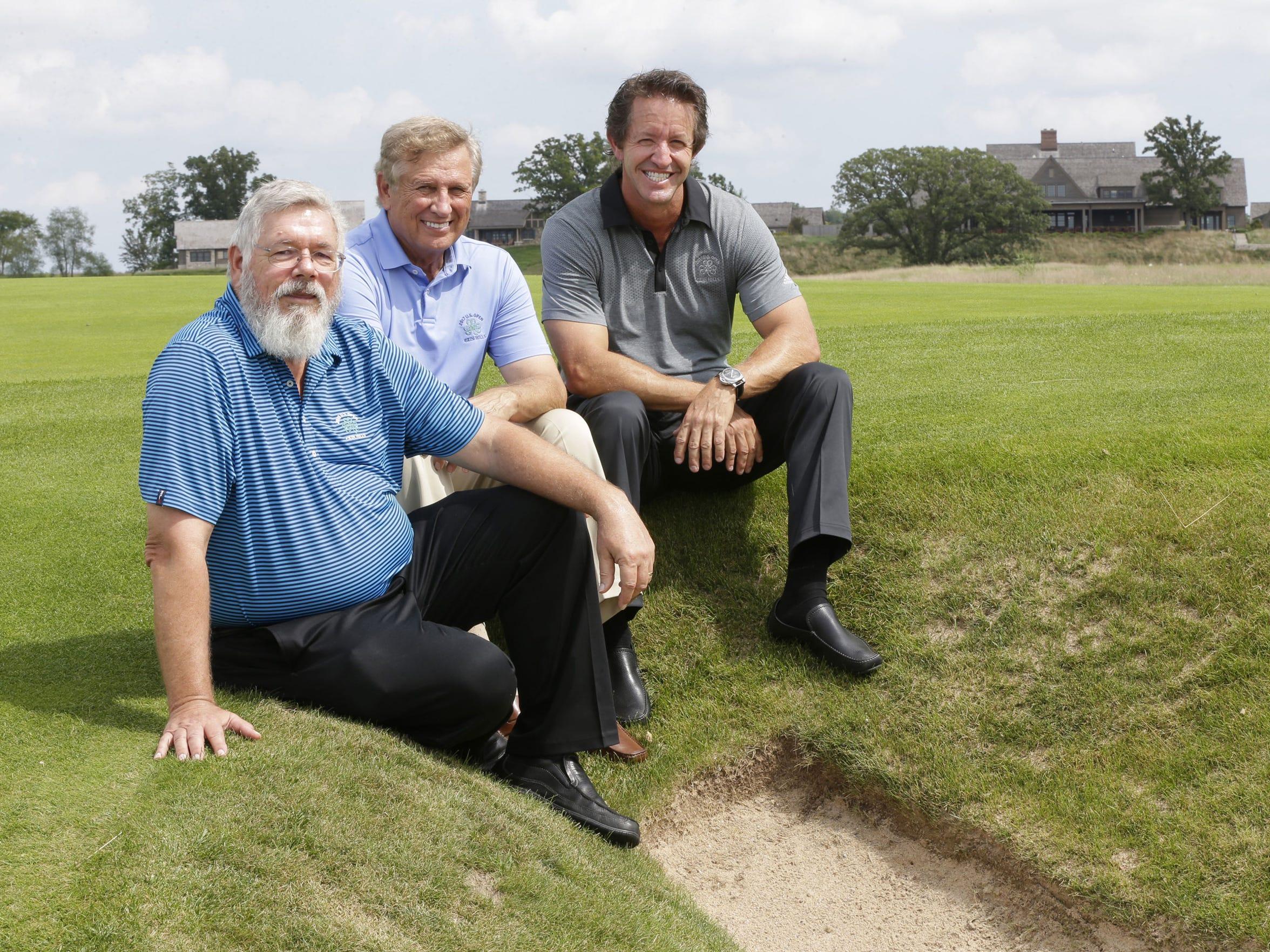 Erin Hills' architects Ron Whitten (from left), Michael Hurdzan and Dana Fry sit next to a bunker on the ninth hole.