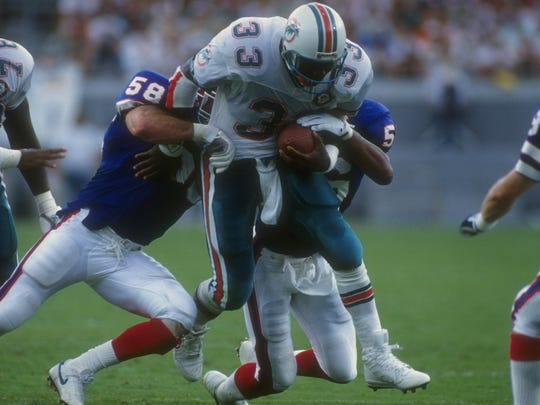Running back Sammie Smith of the Miami Dolphins gets tackled by several Buffalo Bills players.