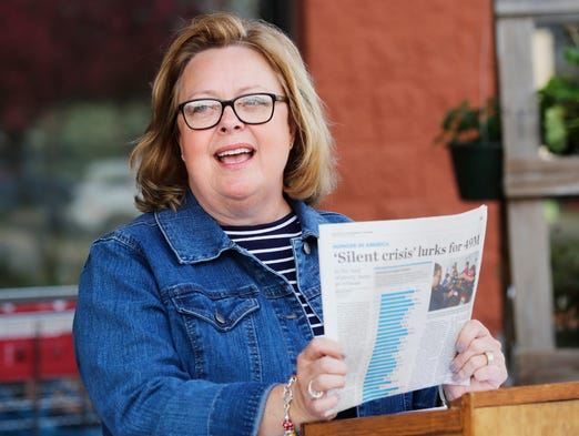 Kim Motuliak, director of operations for Food Finders Food Bank, references a recent newspaper article highlighting the problem of hunger in America as details of the annual Letter Carrier's Food Drive, Stamp Out Hunger, are announced Wednesday, May 7, 2014, at Marsh Supermarket, 3825 South Street in Lafayette. Motuliak said this year's goal is to collect 70,000 lbs. of food, enough to fill two semi trailers.