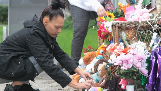 Family member Glenda Burgos of Rochester arranges a memorial at 99 High St., where a mother and two of her children died in an intentionally set house fire in September.