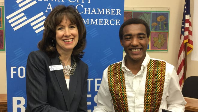 In this 2015 file photo, Nancy Quellhorst, president and CEO of the Iowa City Area Chamber of Commerce, presents an award to Scattergood Friends School student Wubetu Shimelash.