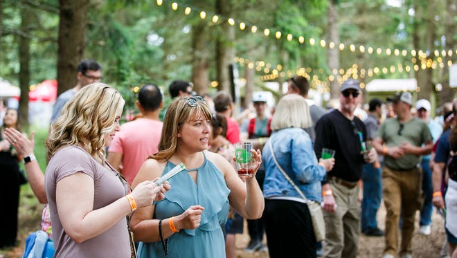 Courtney Christensen, left, and Stephanie Llewellyn, right, decide which beer tastes to choose at the Oregon Garden Brewfest on Saturday, June 17, 2017, in Silverton, Ore.