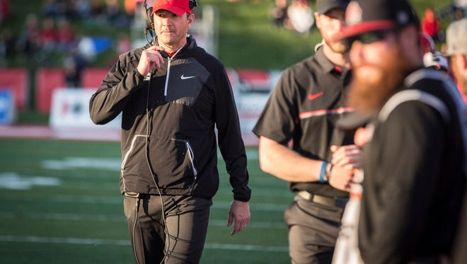 Mike Neu talks with his staff during a play review in the fourth quarter during the homecoming game Saturday afternoon at Scheumann Stadium. Ball State would lose to Akron 35-25.