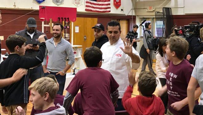 """Cake Boss"" Buddy Valastro high-fives H.B. Whitehorne Middle School students on Nov. 15, 2017."