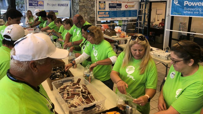 Florida Power & Light Company employees prepare food boxes for the Children's Hunger Project.