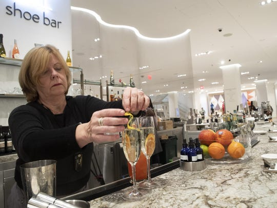 In this Tuesday, Nov. 26, 2019, photo a bartender prepares drinks at the Shoe Bar at the Nordstrom NYC Flagship in New York.